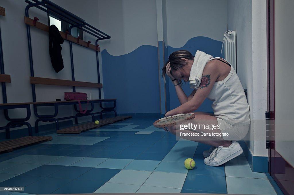 Female tennis player crouching in the locker room : Stock Photo
