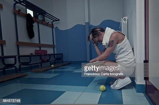 Female tennis player crouching in the locker room