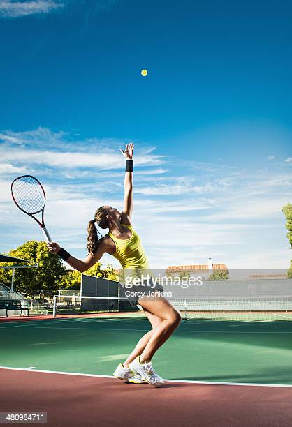 Female tennis player hitting ball