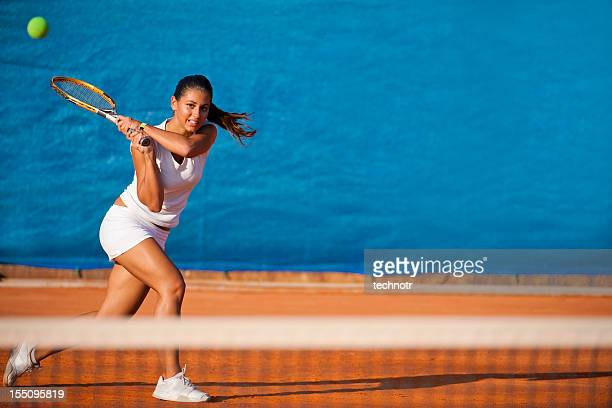Female tennis player hitting the ball