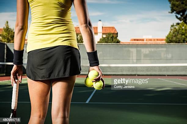 Female tennis player holding balls