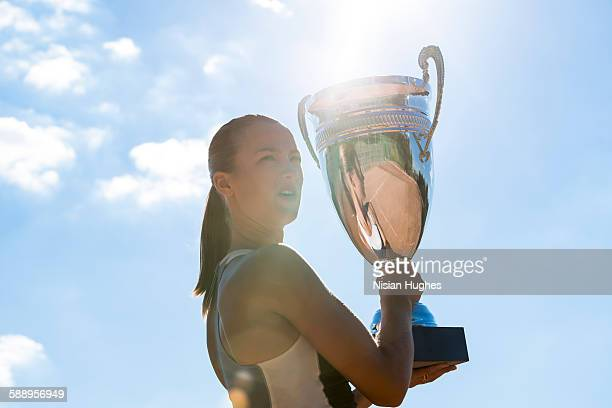 Female tennis player holding up trophy