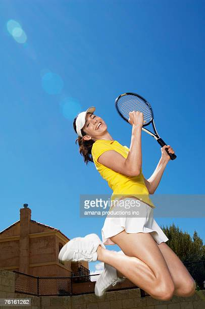 Female tennis player jumping for joy