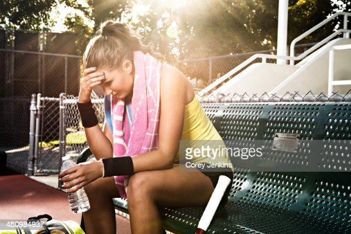 Female tennis player on bench with head in hands
