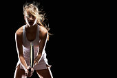 Female tennis player on black background