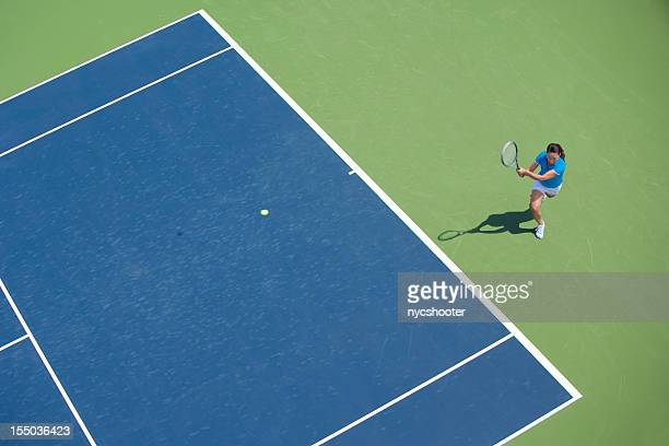 Female tennis player on blue and green court in middle of swing