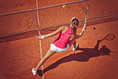 Female tennis player hitting a ball with forehand volley