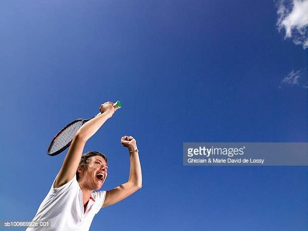 Female tennis player raising arms in air and screaming