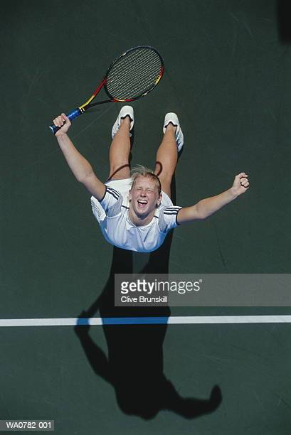Female tennis player raising arms in celebratory pose, overhead view