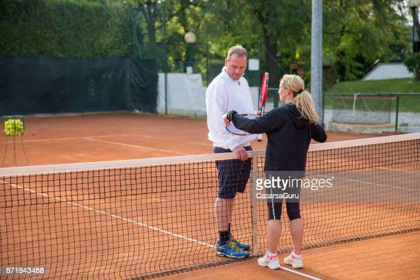 Female Tennis Player Talking With Instructor At The Net On The Tennis Court