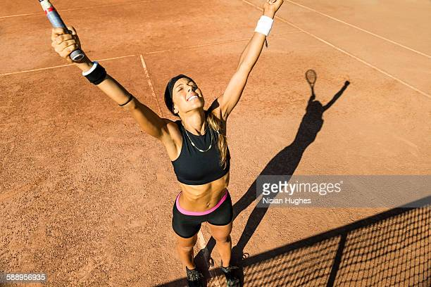 Female tennis player with arms up happy