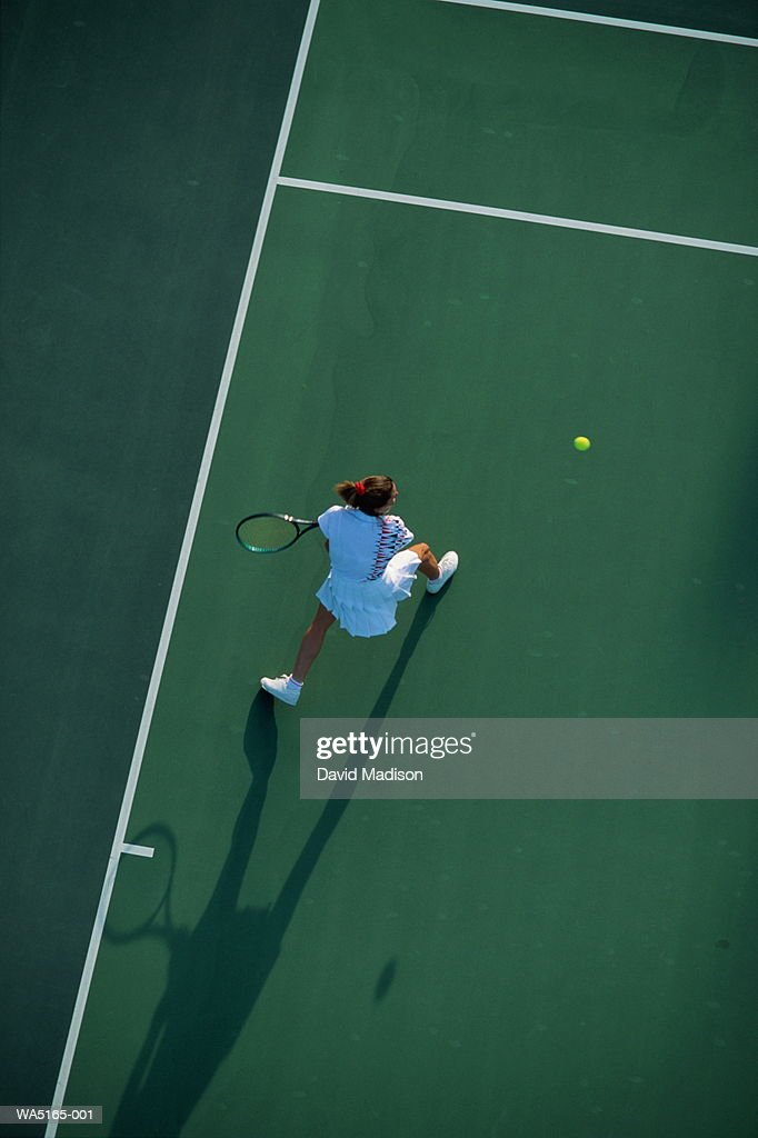 Female tennis player with backhand return, elevated view : Stock Photo