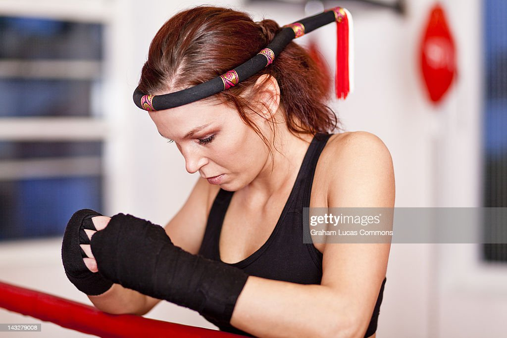 Female Thai boxer wearing a Muay Thai Mongkol : Stock Photo