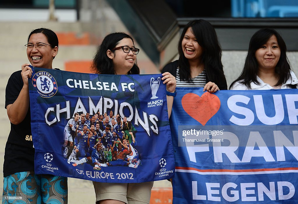 Female Thai fans hold flags during a Chelsea FC training session at Rajamangala Stadium on July 16, 2013 in Bangkok, Thailand.
