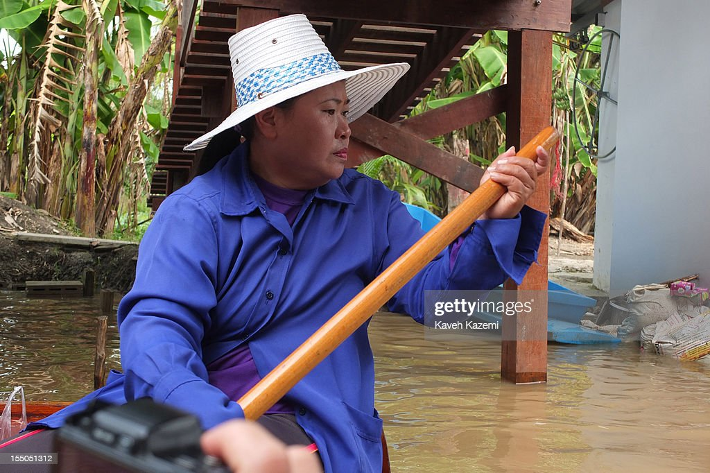 A female Thai vendor rows on her boat in the canals of floating market on October 14 in Damnoen Saduak, Thailand. Damnoen Saduak is a district in the province of Ratchaburi in central Thailand. The central town has become a tourist attraction with its famous floating market.