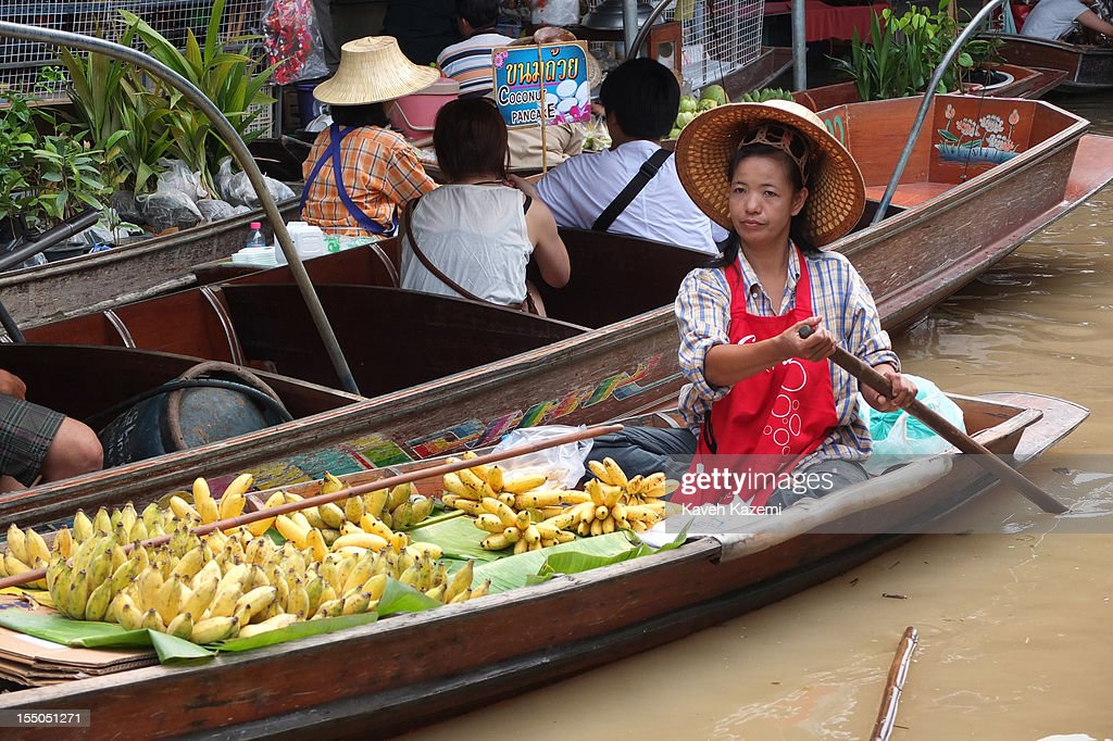 A female Thai vendor rows on her boat selling bananas in the canals of floating market on October 14 in Damnoen Saduak, Thailand. Damnoen Saduak is a district in the province of Ratchaburi in central Thailand. The central town has become a tourist attraction with its famous floating market.
