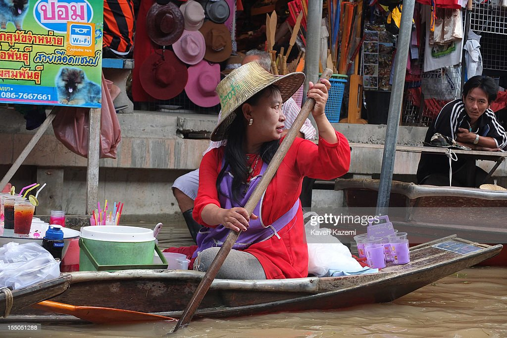 A female Thai vendor rows on her boat selling fruit juices while circulating on the canal in floating market on October 14 in Damnoen Saduak, Thailand. Damnoen Saduak is a district in the province of Ratchaburi in central Thailand. The central town has become a tourist attraction with its famous floating market.