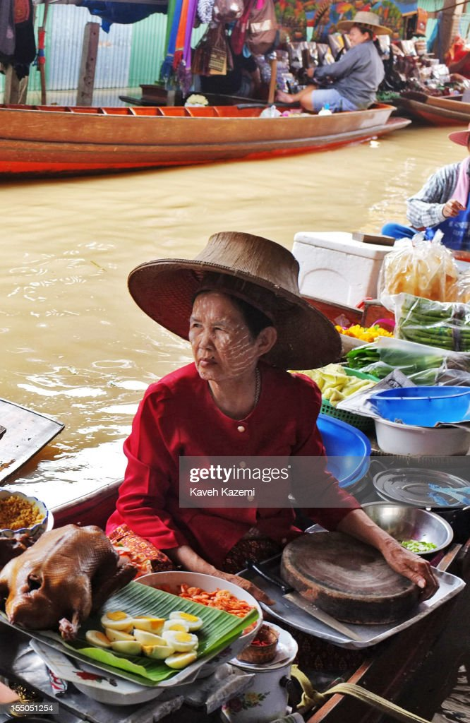 A female Thai vendor selling food on her boat awaits customers in floating market on October 13 in Damnoen Saduak, Thailand. Damnoen Saduak is a district in the province of Ratchaburi in central Thailand. The central town has become a tourist attraction with its famous floating market.