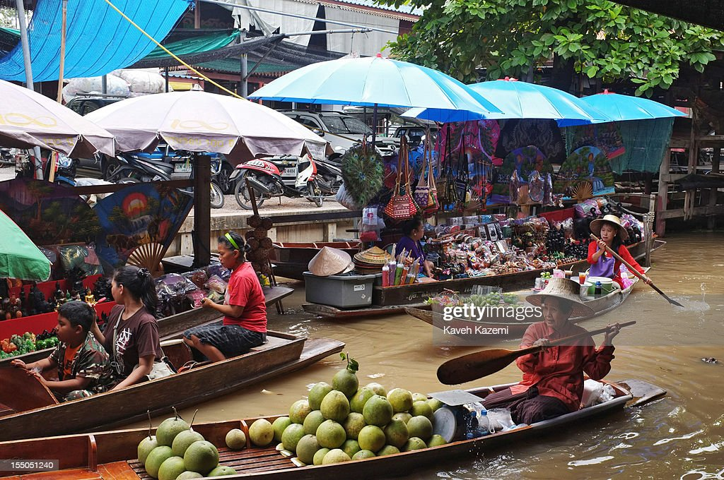A female Thai vendor sells coconuts on her boat while circulating on the canal in floating market on October 13 in Damnoen Saduak, Thailand. Damnoen Saduak is a district in the province of Ratchaburi in central Thailand. The central town has become a tourist attraction with its famous floating market.