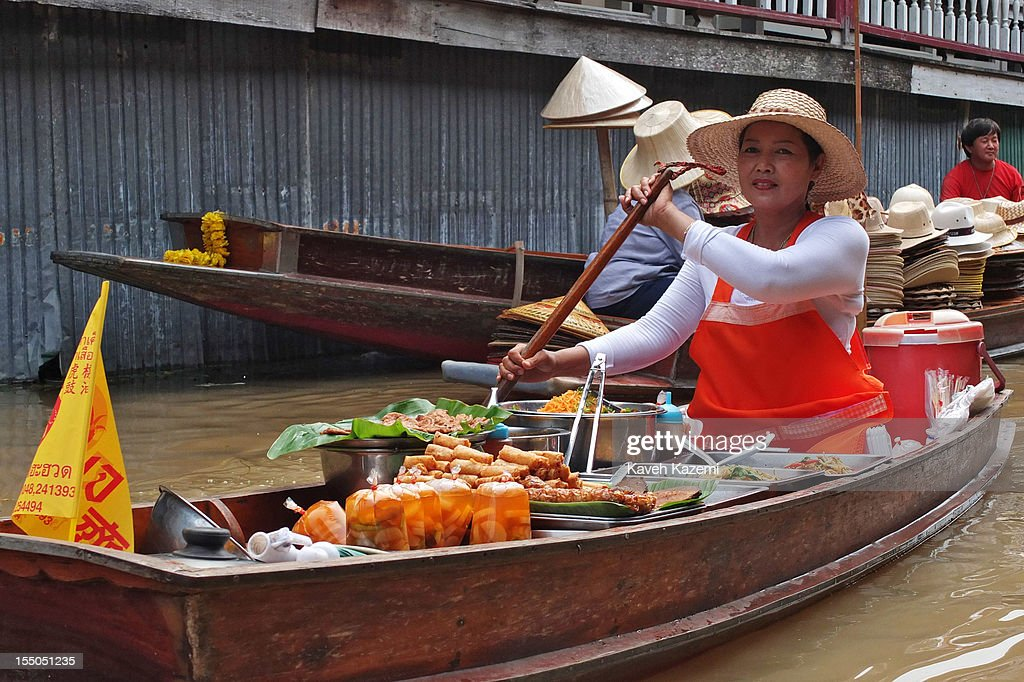 A female Thai vendor sells food on her boat while circulating on the canal in floating market on October 13 in Damnoen Saduak, Thailand. Damnoen Saduak is a district in the province of Ratchaburi in central Thailand. The central town has become a tourist attraction with its famous floating market.