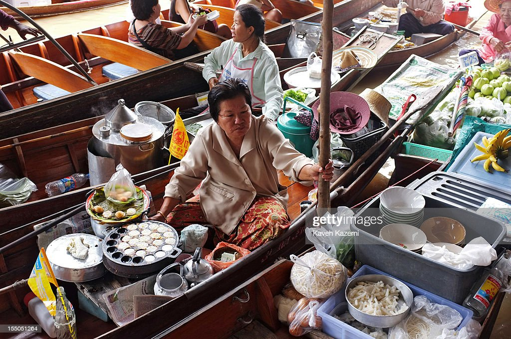 Female Thai vendors sell food, vegetables and fruits on their boats while circulating on the canal in floating market on October 13 in Damnoen Saduak, Thailand. Damnoen Saduak is a district in the province of Ratchaburi in central Thailand. The central town has become a tourist attraction with its famous floating market.