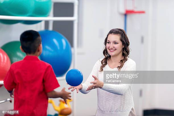 Female therapist tossing a ball to a young hispanic male