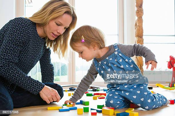 Female toddler and mother playing with building bricks on living room floor