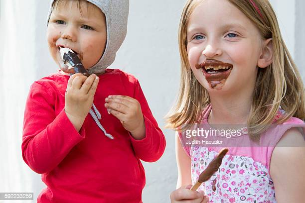 Female toddler and sister messily eating chocolate ice creams