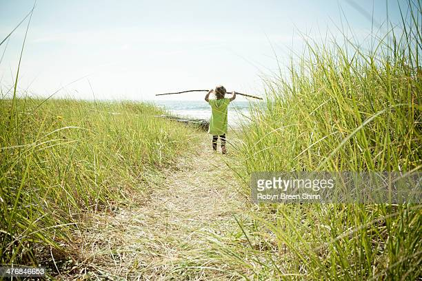 Female toddler carrying long stick