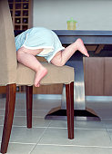 Female toddler (21-24 months) climbing on chair, rear view