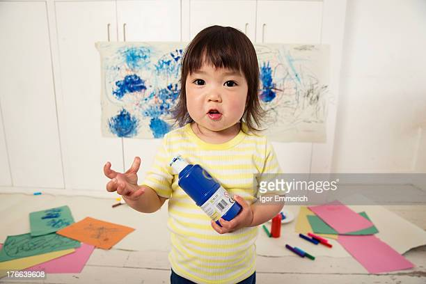 Female toddler holding paint bottle
