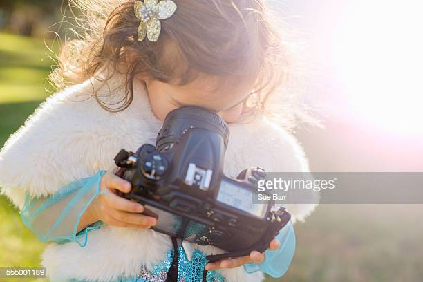 Female toddler in garden peering down into camera lens