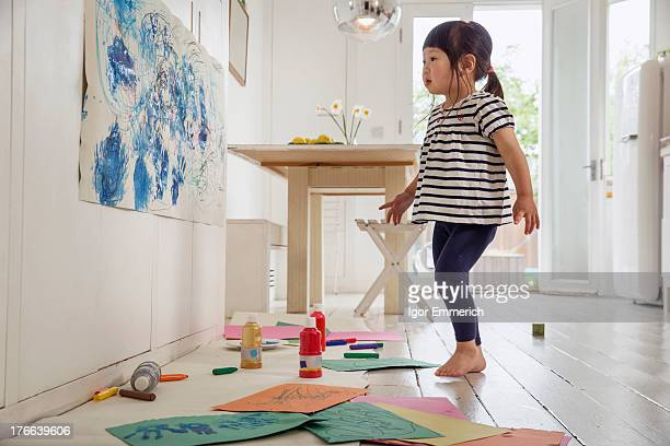 Female toddler inspecting her painting and drawing