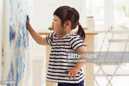 Female toddler making handprint painting