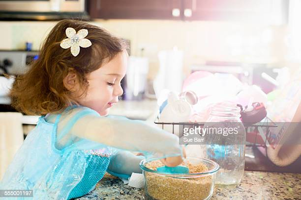 Female toddler mixing baking ingredients at kitchen counter