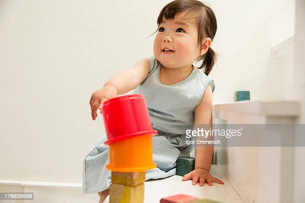 Female toddler on stairs building tower