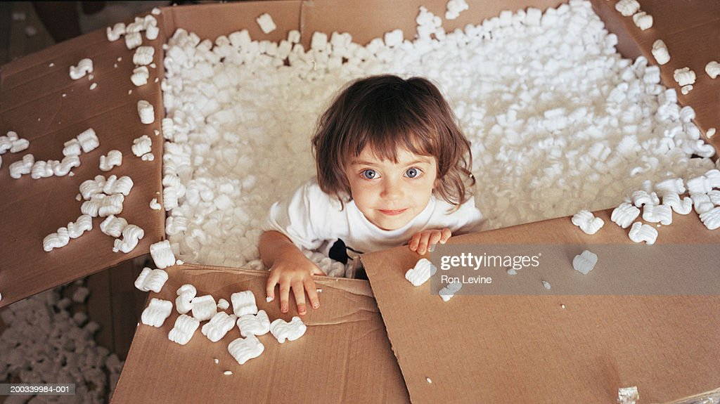 Female toddler (21-24 months) playing in foam packing, portrait : Stock Photo