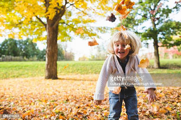 Female toddler playing with autumn leaves