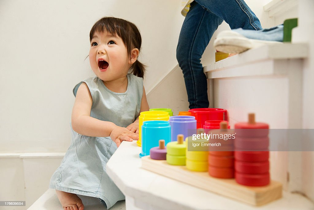 Female toddler playing with toys on staircase