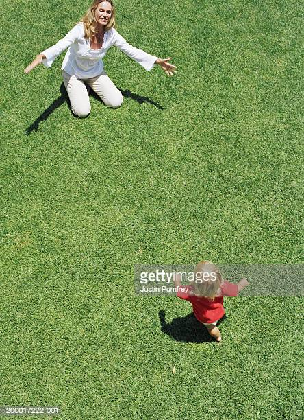 Female toddler (18-21 months) running across lawn towards mother
