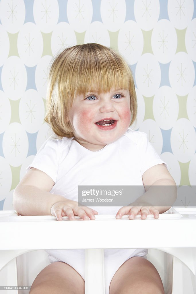 Female toddler (12-15 months) sitting in high chair, smiling, close-up