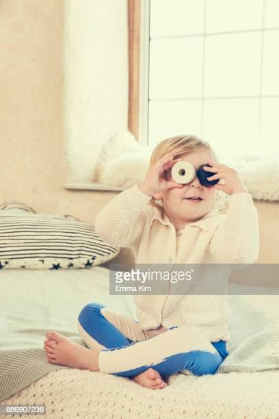 Female toddler sitting on bed peeking through circles covering eyes