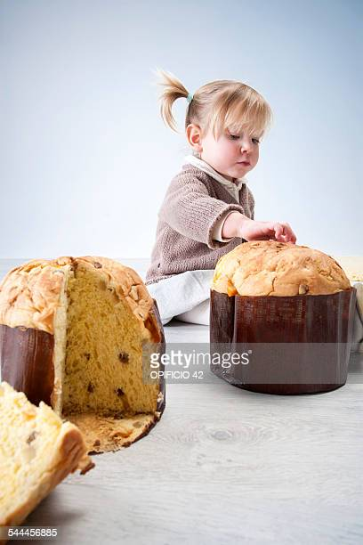 Female toddler sitting on floor with fingers on pannetone cake