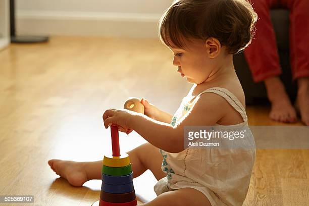 Female toddler sitting on living room floor playing with toy building rings
