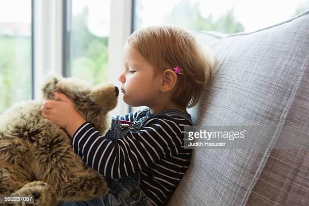 Female toddler sitting on sofa kissing teddy bear