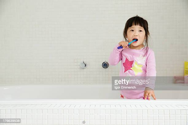 Female toddler standing in bath brushing teeth