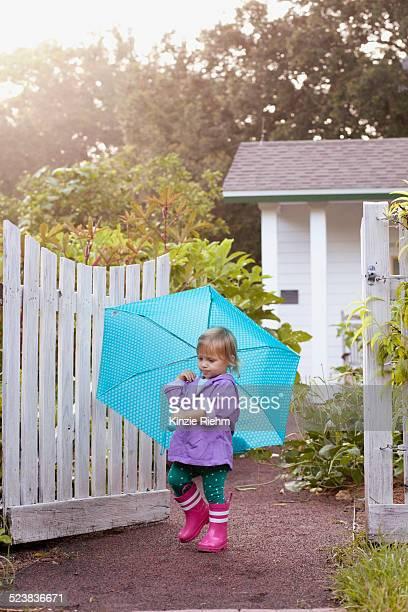 Female toddler walking in garden carrying umbrella