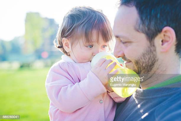 Female toddler with father drinking baby bottle in park