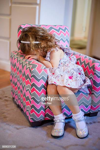 Female toddler with hiding her face on childs armchair