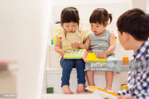 Female toddlers on stairs with game book